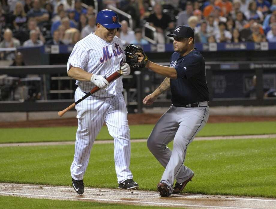 New York Mets pitcher Bartolo Colon, left, is tagged out by Atlanta Braves pitcher Williams Perez on a sacrifice bunt by Colon during the second inning of a baseball game Wednesday, Sept. 23, 2015, in New York. (AP Photo/Bill Kostroun)