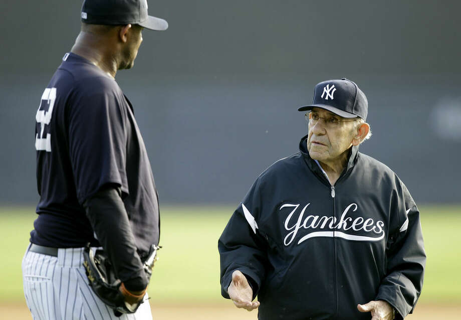File-This Feb. 24, 2011, file photo shows New York Yankees pitcher CC Sabathia,left, talking with Yogi Berra, right, during a baseball spring training workout at Steinbrenner Field in Tampa, Fla. Berra, the Yankees Hall of Fame catcher has died. He was 90.(AP Photo/Charlie Neibergall, File)
