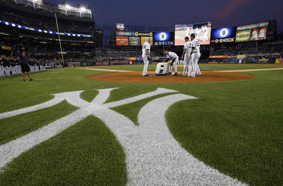 New York Yankees manager Joe Girardi places flowers on home plate in remembrance of Yogi Berra prior to a baseball game against the Chicago White Sox on Thursday, Sept. 24, 2015, in New York. Berra, a Hall of Fame catcher for the Yankees, died Tuesday. (AP Photo/Adam Hunger)