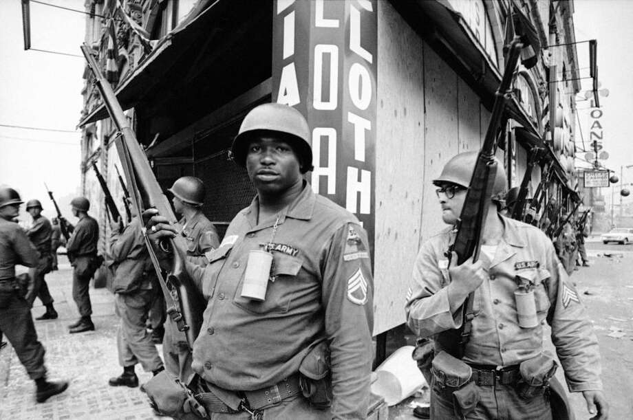 FILE - This July 14, 1967 file photo shows National Guardsmen patroling Newark, July 14, 1967, after a Newark detective was shot by sniper's bullet. They stand at the corner of Springfield Avenue and Mercer Street, an area hit by looting and rioting in the past two days. The St. Louis suburb of Ferguson, Missouri, was roiled by racial unrest after 18-year-old Michael Brown, who was black, was shot and killed by Darren Wilson, a white police officer, on Aug. 9. The street clashes there mirrored past, larger-scale riots in multiple US cities, most of them triggered by perceived racial injustice, or an incident involving police, in already tense communities. (AP Photo/Marty Lederhandler, File)