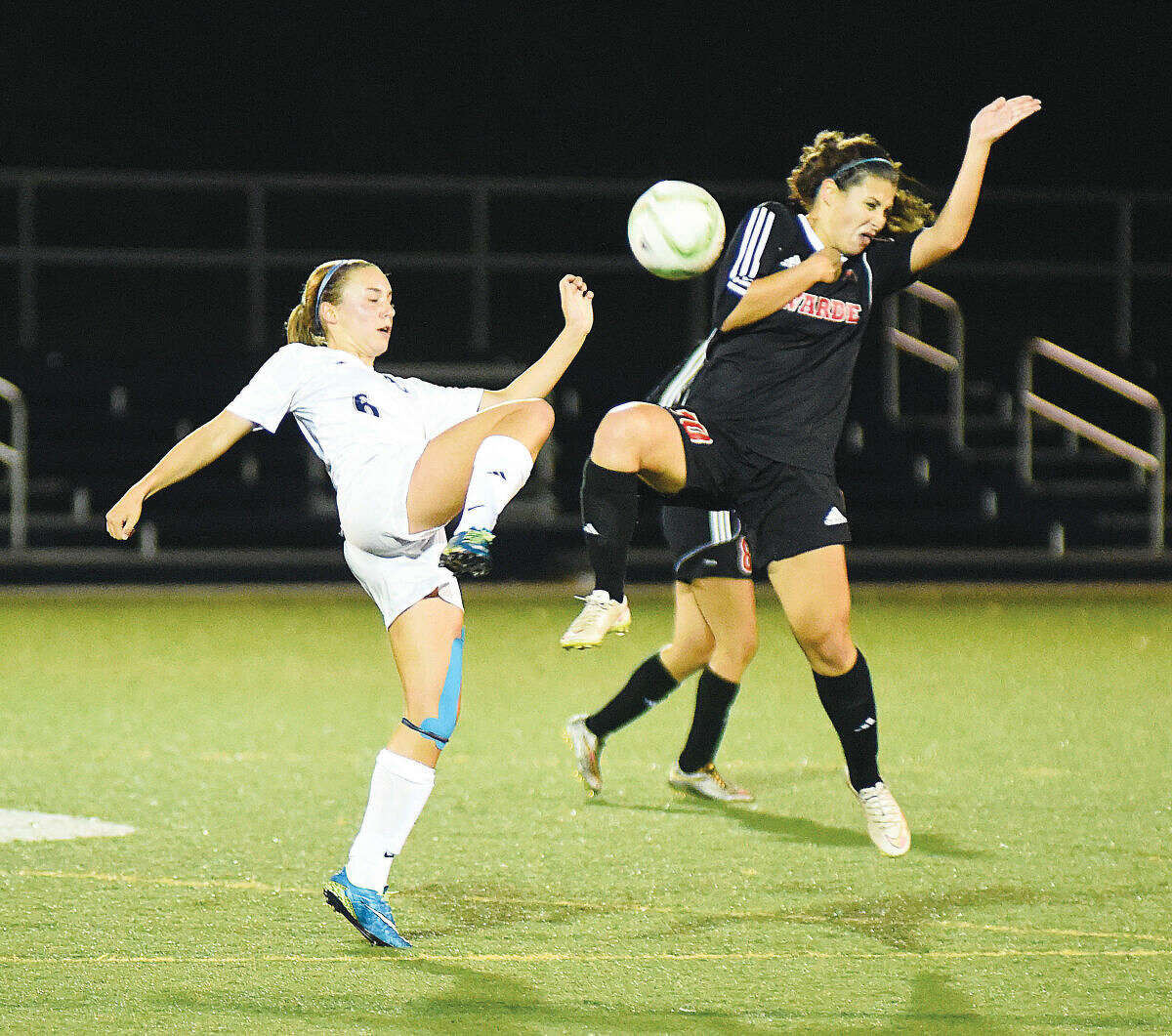 Hour photo/John Nash - Wilton's Lyndsey Groves, left, and Fairfield Warde's Amelia Andrews during Thursday's FCIAC girls soccer game at Lilly Field in Wilton.