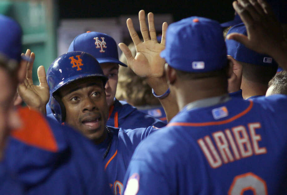 New York Mets Curtis Granderson gets congratulated by teammates after scoring against the Cincinnati Reds in the seventh inning of a baseball game in Cincinnati, Thursday, Sept. 24, 2015. (AP Photo/Tom Uhlman)
