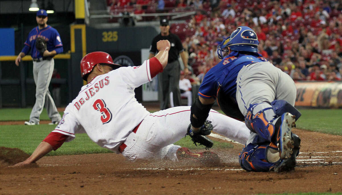Cincinnati Reds Ivan De Jesus slides saftly into home plate as New York Mets catcher Travis d'Amaud misses the tag in the first inning of their baseball game in Cincinnati, Thursday, Sept. 24, 2015. (AP Photo/Tom Uhlman)