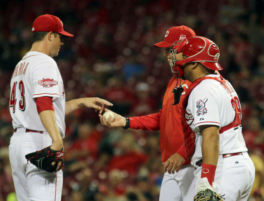 Cincinnati Reds Manny Parra get taken out of the game by manager Bryan Price and catcher Brayan Pena against the New York Mets in the seventh inning of a baseball game in Cincinnati, Thursday, Sept. 24, 2015. (AP Photo/Tom Uhlman)
