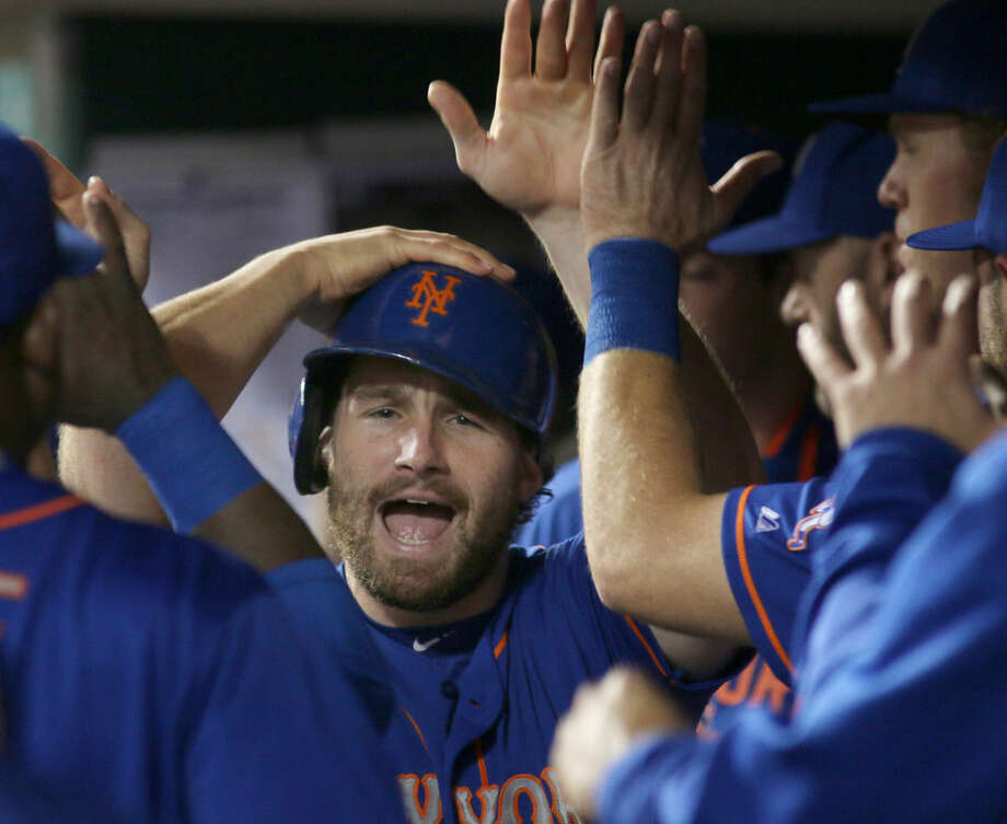 New York Mets Daniel Murphy gets congratulated by teammates after scoring against the Cincinnati Reds in the seventh inning of a baseball game in Cincinnati, Thursday, Sept. 24, 2015. (AP Photo/Tom Uhlman)