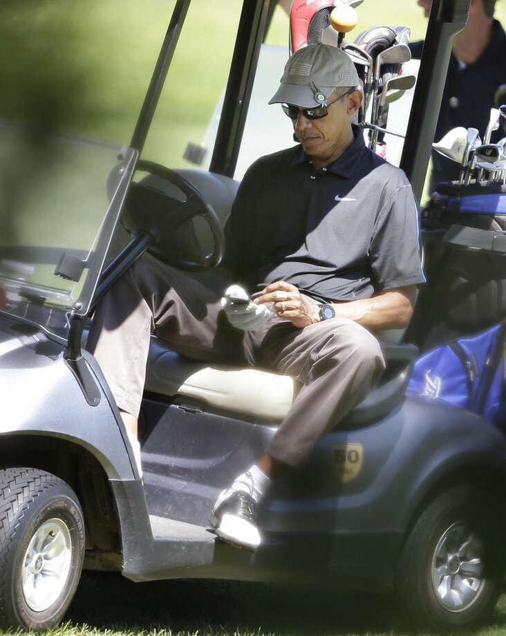 President Barack Obama operates an electronic device while golfing at Farm Neck Golf Club, in Oak Bluffs, Mass., on the island of Martha's Vineyard, Thursday, Aug. 21, 2014. Obama is vacationing on the island. (AP Photo/Steven Senne)