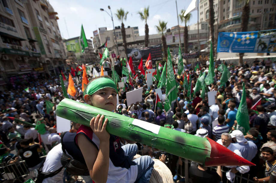 A Palestinian boy, along with supporters of Hamas, holds a representation of a rocket as others shout slogans to protest against Israel and to support people in Gaza, during a demonstration in the West Bank city of Ramallah, Friday, Aug. 22, 2014. (AP Photo/Majdi Mohammed)