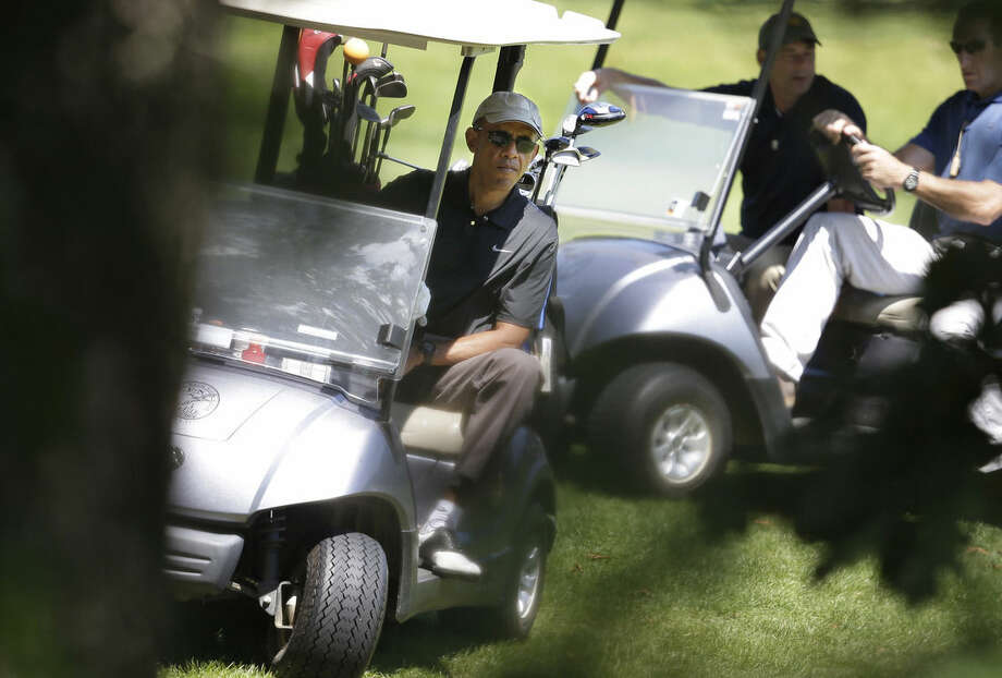 President Barack Obama, left, maneuvers his golf cart while golfing at Farm Neck Golf Club, in Oak Bluffs, Mass., on the island of Martha's Vineyard, Thursday, Aug. 21, 2014. Obama is vacationing on the island. (AP Photo/Steven Senne)