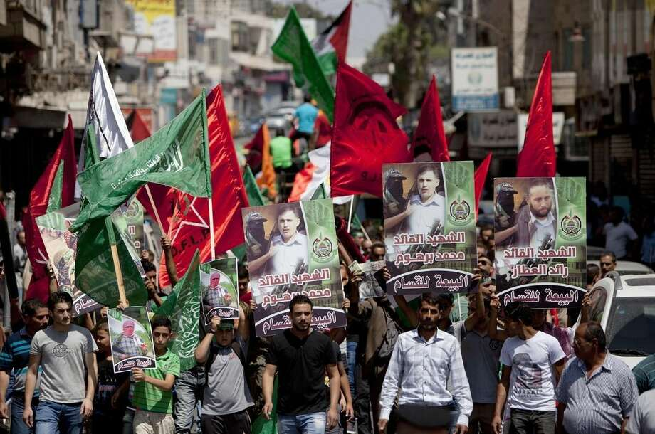 Supporters of Hamas hold posters of three senior commanders of the Hamas military wing, Mohammed Abu Shamaleh, Raed Attar and Mohammed Barhoum, who were killed in Thursday's Israeli strikes, during a demonstration to protest against Israel and to support people in Gaza, in the West Bank city of Ramallah on Friday, Aug. 22, 2014. (AP Photo/Majdi Mohammed)