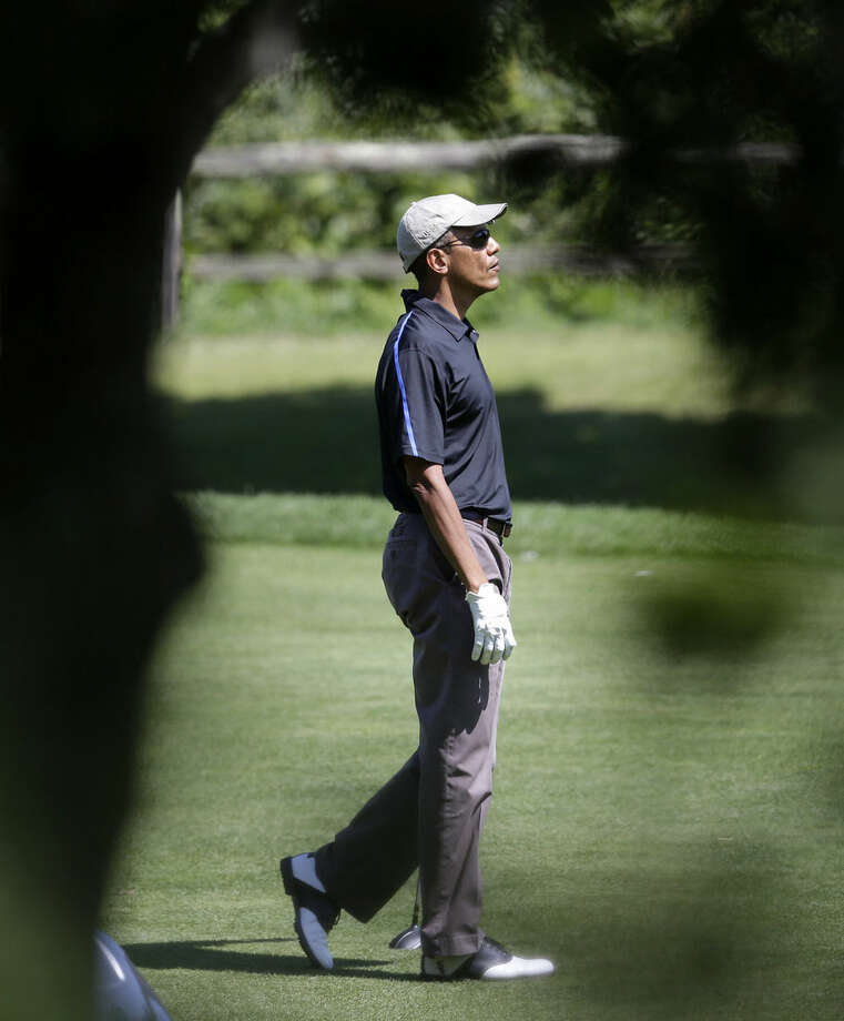 President Barack Obama watches the flight of his ball after hitting on the fairway while golfing at Farm Neck Golf Club, in Oak Bluffs, Mass., on the island of Martha's Vineyard, Thursday, Aug. 21, 2014. Obama is vacationing on the island. (AP Photo/Steven Senne)