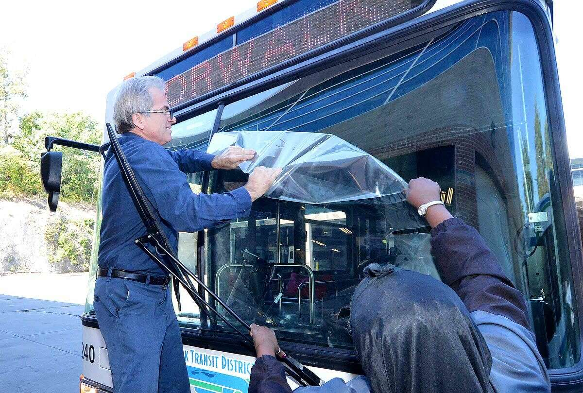 Hour Photo/Alex von Kleydorff Two more of the 12 new Low Floor Shuttle vehicles arrives at WHEELS headquarters on Thursday afternoon and Maintenance Foreman Tony Merturi gets help removing the protective plastic sheeting used to keep the windshield free from chips while in transport from Donna Okeke who just drove the bus almost 3000 miles from the Gillig facility in Hayward Calif.