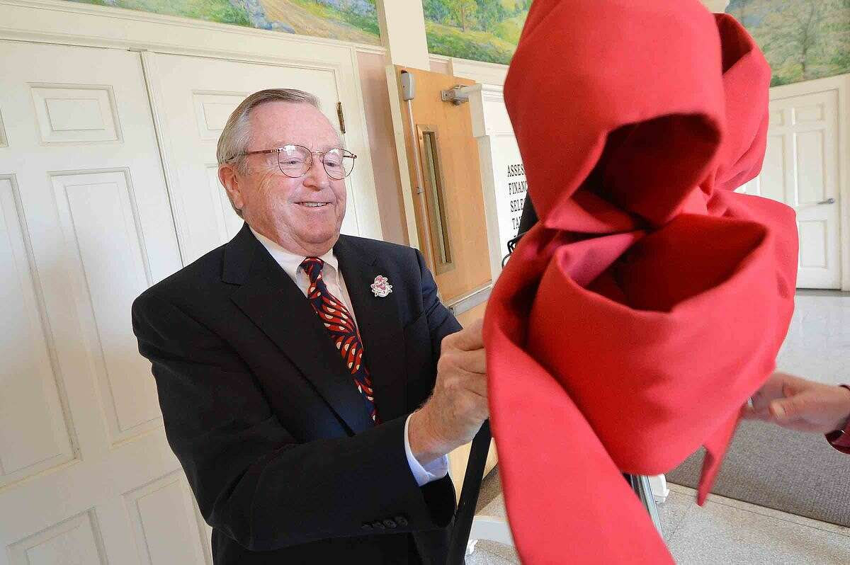 First Selectman Bill Brennan tightens a big red bow at the Wilton Holiday Fund kick-off.