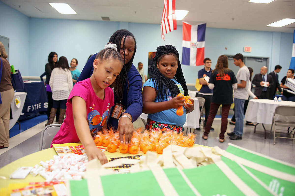 Yahira Vazquez, 8, Eva Beau and Tamia Thorne, 8, from the Norwalk Community Health Center, fix their table during the Latinos Unidos de Connecticut fair at the South Norwalk Community Center Thursday evening. Hour Photo / Danielle Robinson Calloway