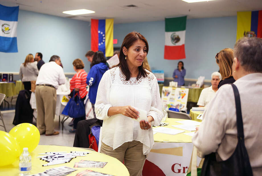 Kids in Crisis Social Worker Ingrid Pasten, speaks to a guest during the Latinos Unidos de Connecticut fair at the South Norwalk Community Center Thursday evening. Hour Photo / Danielle Robinson Calloway
