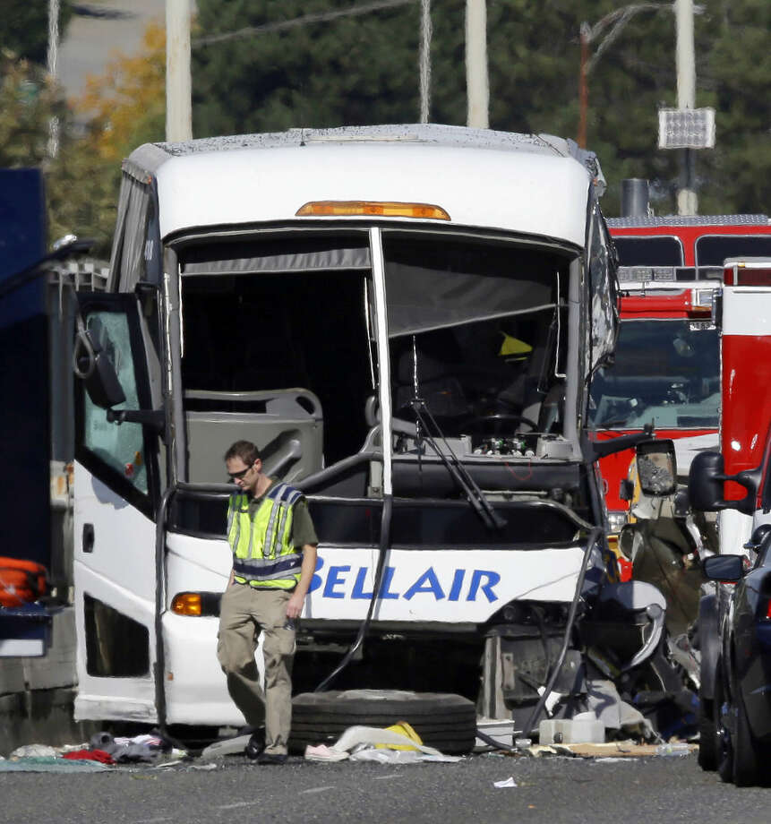 """An emergency worker walks in front of a charter bus that was involved in a fatal crash with a """"Ride the Ducks"""" amphibious tour bus, Thursday, Sept. 24, 2015, in Seattle. (AP Photo/Ted S. Warren)"""
