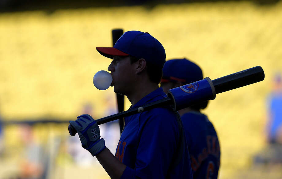 New York Mets' Wilmer Flores blows bubbles as he waits to hit during batting practice for a baseball game against the Los Angeles Dodgers, Friday, Aug. 22, 2014, in Los Angeles. (AP Photo/Mark J. Terrill)