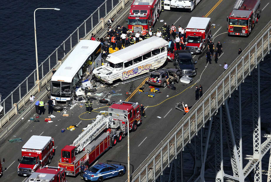 """Emergency personnel work at the scene of a fatal collision involving a charter bus, center left, and a """"Ride the Ducks"""" amphibious tour bus on the Aurora Bridge in Seattle on Thursday, Sept. 24, 2015. (Ken Lambert/The Seattle Times via AP) SEATTLE OUT; USA TODAY OUT; MAGAZINES OUT; NO SALES; TELEVISION OUT; MANDATORY CREDIT: KEN LAMBERT/THE SEATTLE TIMES"""