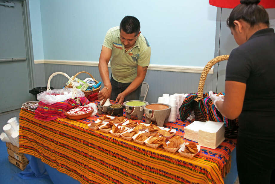 Juan Bautista from Los Poblanos sets up some chips and salsa during the Latinos Unidos de Connecticut fair at the South Norwalk Community Center Thursday evening. Hour Photo / Danielle Robinson Calloway