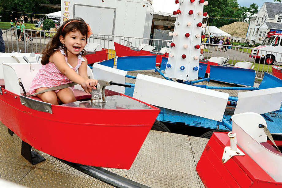 Hour photo / Erik Trautmann 3 year old Isabella Leia Rodriguez steers the boat ride at the St. George Greek Orthodox Church annual Greek festival Saturday.