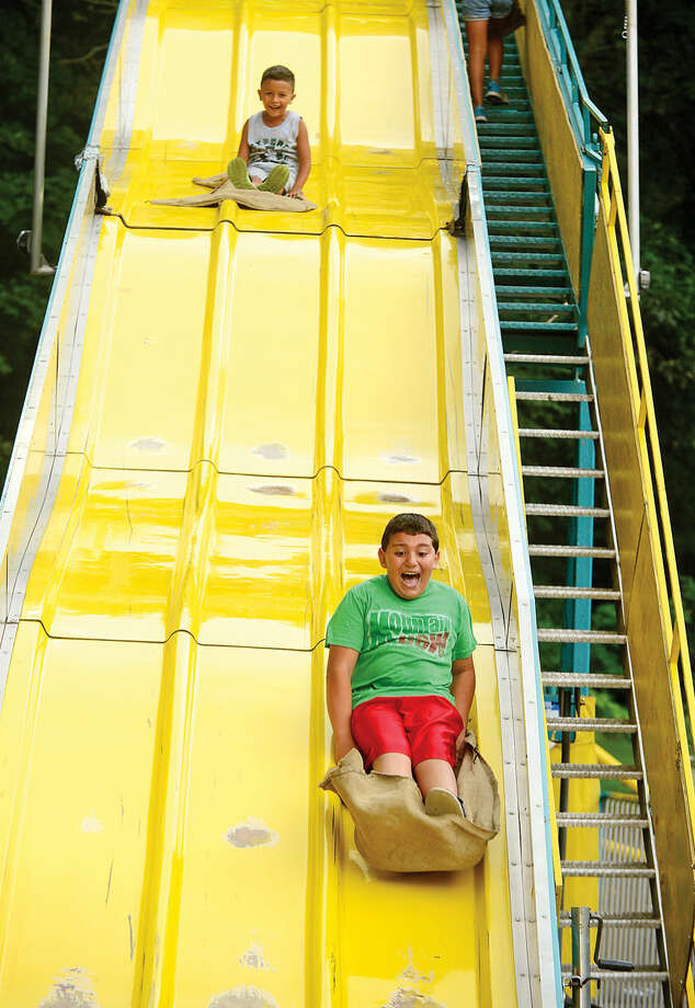 Hour photo / Erik Trautmann Giovanni Androni and Evandros Velez come down the Giant Slide at the St. George Greek Orthodox Church annual Greek festival Saturday.