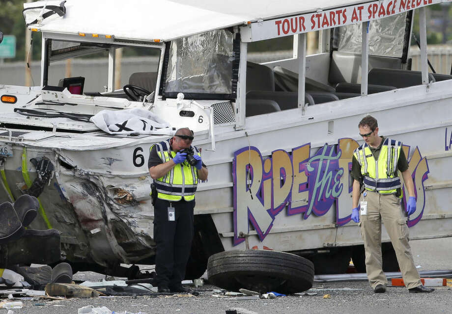Seattle Police investigators photograph the front tire from a Ride the Ducks tour bus as it lies on the ground following a fatal crash involving the tour bus and several other vehicles, Thursday, Sept. 24, 2015 in Seattle. (AP Photo/Ted S. Warren)