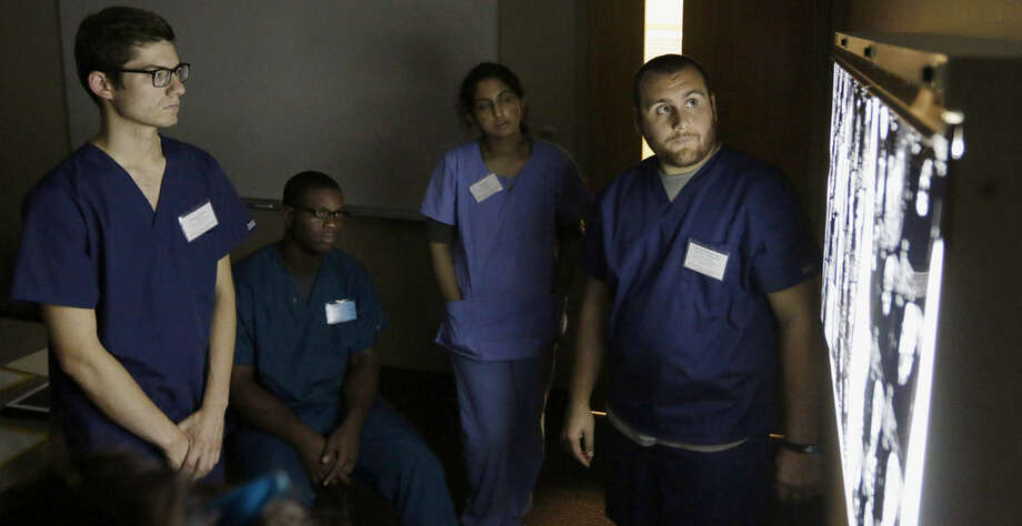 In this July 30, 2014 photo, a group of students look over X-rays during the 2014 International Human Cadaver Prosection Program at the medical school at Indiana University Northwest in Gary, Ind. Included is a high school student named Johntrell Bowles, center, who applied for the program because he'd like to be a doctor one day. (AP Photo/Stacy Thacker)