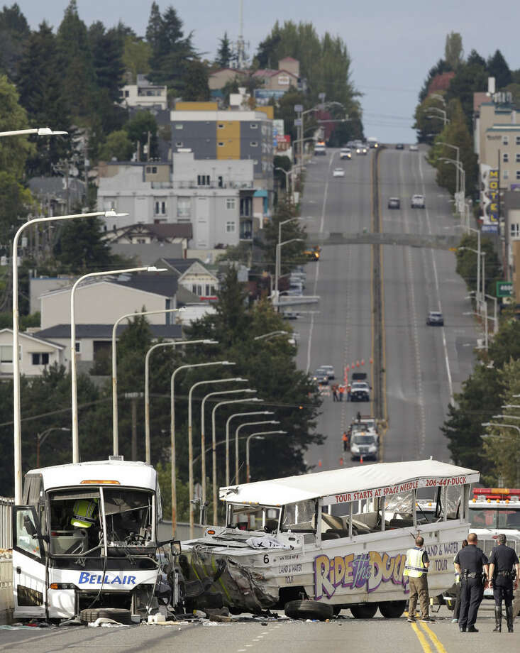 A tour bus, right, and a chartered passenger bus, left, remain on the Aurora Ave. Bridge following a fatal crash earlier in the day, Thursday, Sept. 24, 2015 in Seattle. (AP Photo/Ted S. Warren)