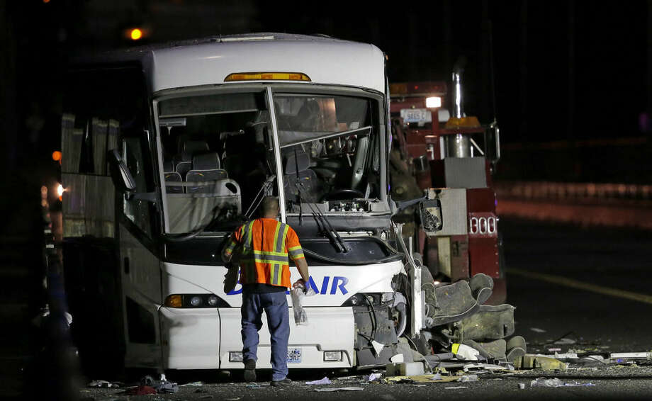 """A towing worker stands in front of a charter passenger bus that was involved in a fatal crash with a """"Ride the Duck""""s tourist vehicle earlier in the day, Thursday, Sept. 24, 2015, in Seattle. (AP Photo/Ted S. Warren)"""