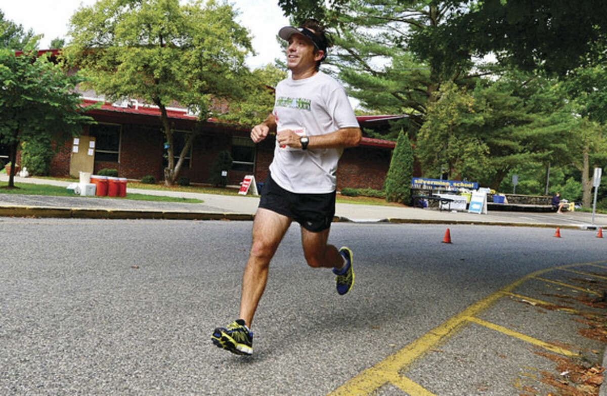 Hour photo / Erik Trautmann Eric Boucher nears the finish line during the Lightfoot Road Running Series 11-mile race Saturday at Silvermine Elementary School.