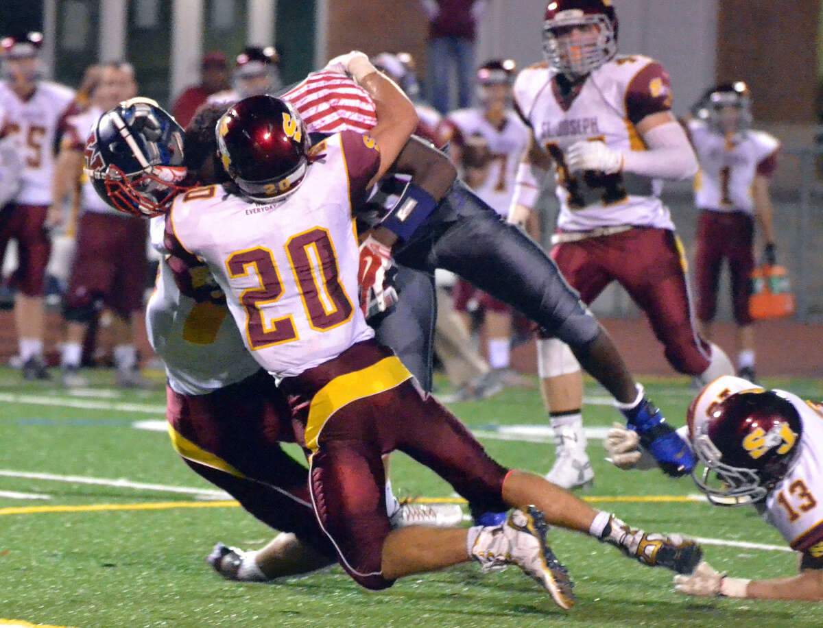 Brien McMahon's Jared Fields is tackled by St. Joseph's Christian Trefz. (Pete Paguaga/Hour photo)