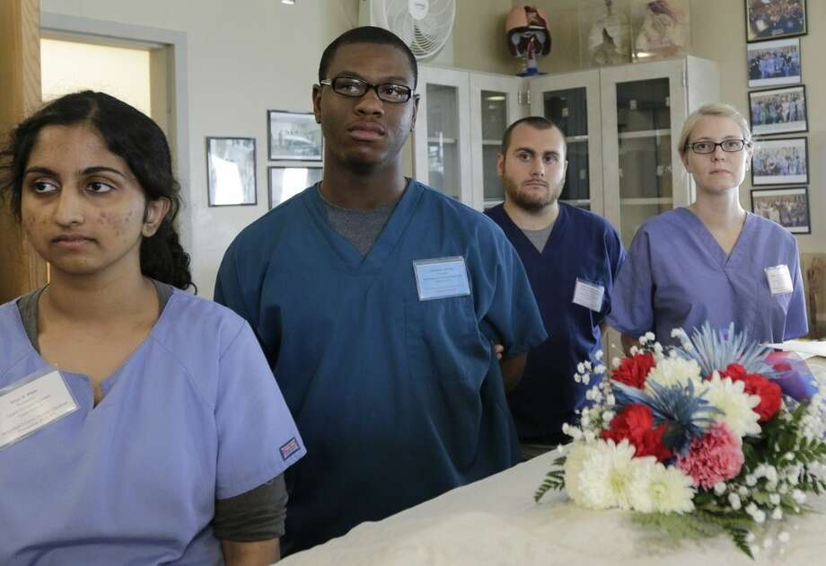 In this July 30, 2014 photo, a group of students, doctors, and nurses attend a ceremony in the gross anatomy lab honoring those who donated their bodies to science during the 2014 International Human Cadaver Prosection Program at the medical school at Indiana University Northwest in Gary, Ind. Included is a high school student named Johntrell Bowles, center, who applied for the program because he'd like to be a doctor one day. (AP Photo/Stacy Thacker)