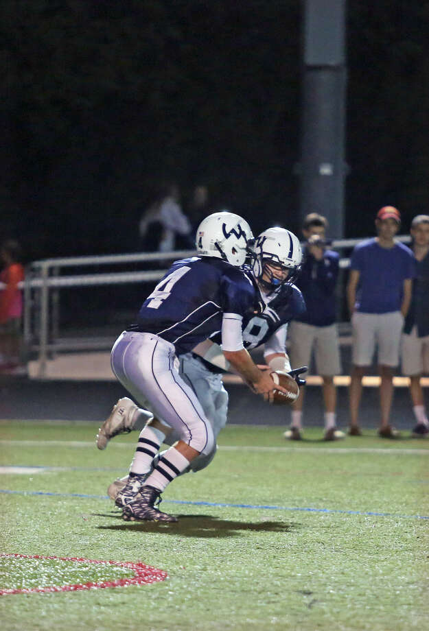 Wilton's #4, Rj Romeo, hands off to #8, Joe Mcfadden, during a game against Staples at Fujitani Field Friday evening. Hour Photo / Danielle Calloway