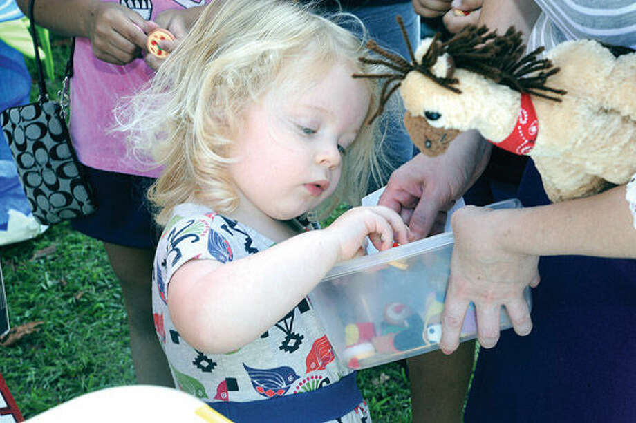 Amelia Schneekloth 3, digs for something good with her parents Sunday at the eigth old fashioned flea market held on the grounds at Mathews Park in Norwalk. Hour photo/Matthew Vinci
