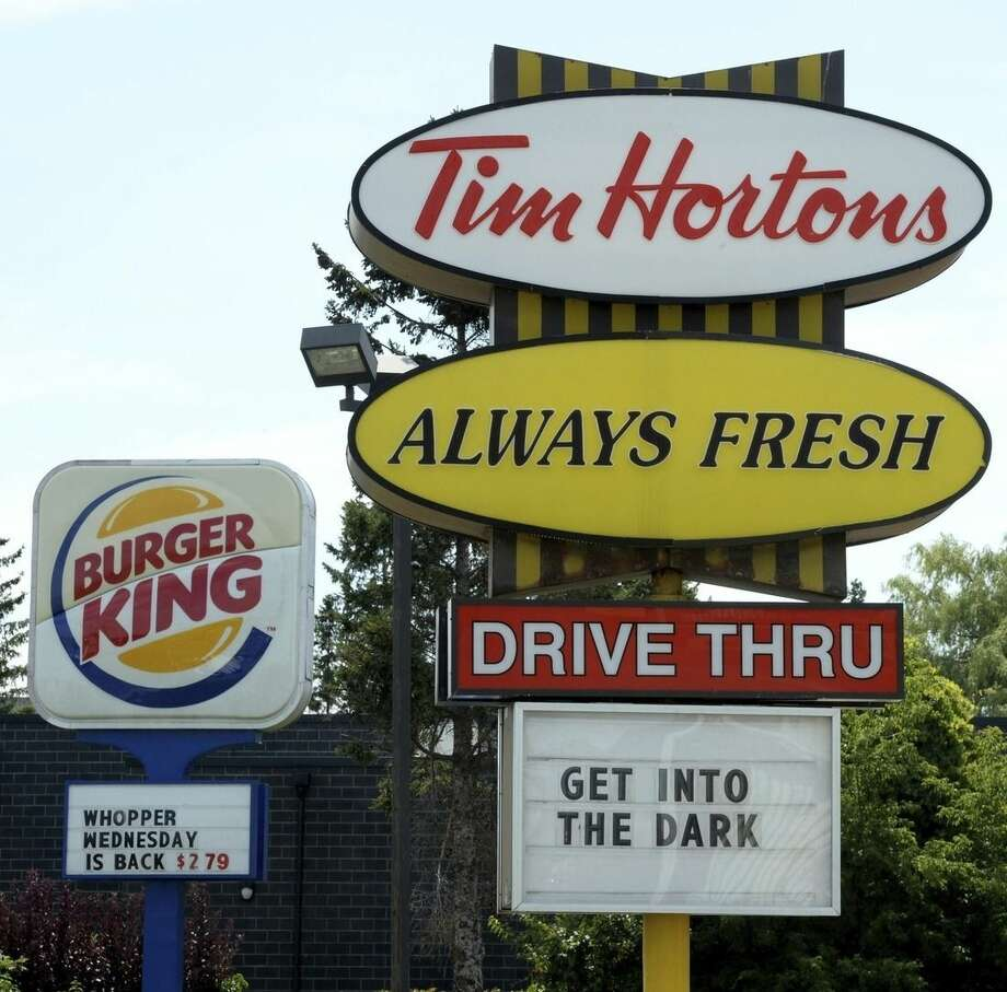 A Burger King sign and a Tim Hortons sign are displayed on St. Laurent Boulevard in Ottawa, Canada, on Monday, Aug. 25, 2014. Canada's iconic coffee chain, Tim Hortons, and Miami-based Burger King say they will join forces, but will operate as independent brands to form the world's third-largest quick service restaurant company. (AP Photo/The Canadian Press, Sean Kilpatrick)