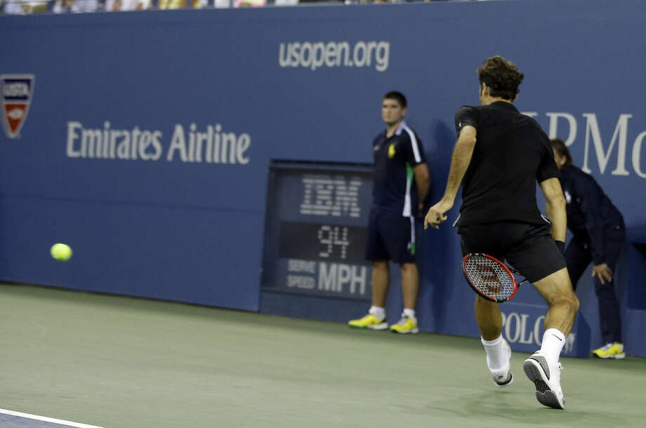 Roger Federer, of Switzerland, returns a shot between his legs to Marinko Matosevic, of Australia, during the first round of the 2014 U.S. Open tennis tournament Tuesday, Aug. 26, 2014, in New York. (AP Photo/Darron Cummings)