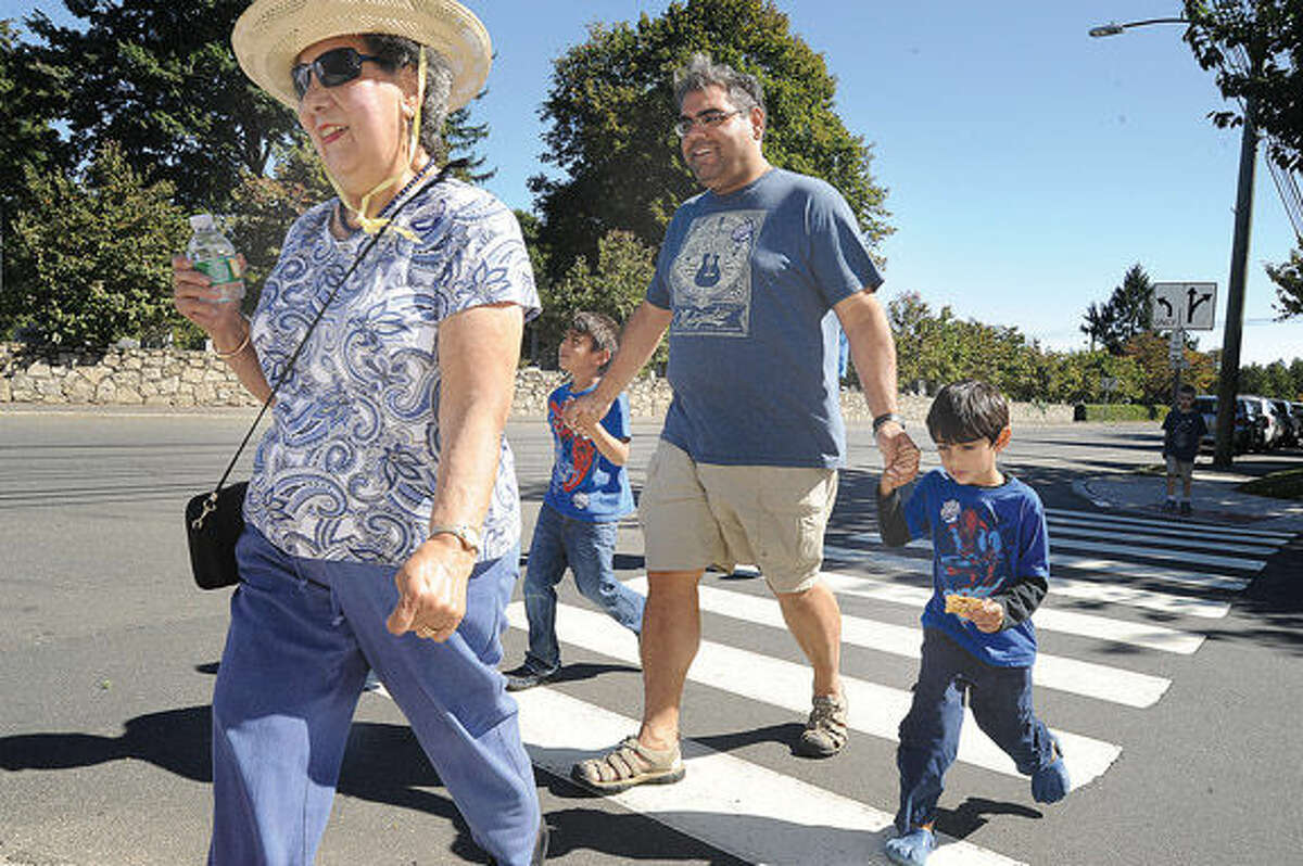 Carmine Shute, Adil Khan and his sons, Nasif 3 and Nabeel 6, participate in the East United Methodist Church's Norwalk CROP Hunger Walk on Sunday making their way down East Avenue. Hour photo/Matthew Vinci