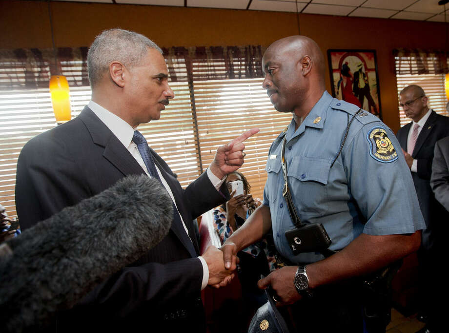 FILE - This Aug. 20, 2014 file-pool photo shows Attorney General Eric Holder talking with Capt. Ron Johnson of the Missouri State Highway Patrol at Drake's Place Restaurant in Florrissant, Mo. As the Justice Department probes the police shooting of an unarmed 18-year-old in Ferguson, Missouri, history suggests there's no guarantee of a criminal prosecution, let alone a conviction. Federal authorities investigating possible civil rights violations in the Aug. 9 death of Michael Brown must meet a difficult standard of proof, a challenge that has complicated the path to prosecution in past police shootings. (AP Photo/Pablo Martinez Monsivais, File-Pool)