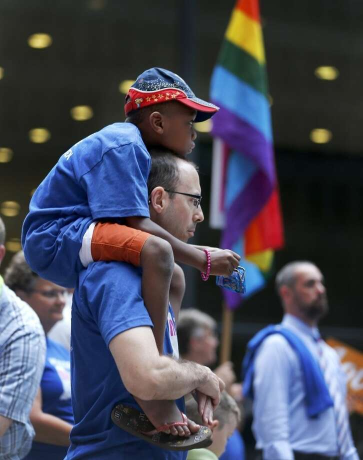 George Sloan, from Chicago, holds his son Sloan D'Souza on his shoulders as they attend a rally in support of gay marriage in Wisconsin and Indiana, at the federal plaza Monday, Aug. 25, 2014, in Chicago. The Chicago-based 7th U.S. Circuit Court of Appeals will hear arguments Tuesday on gay marriage fights from Indiana and Wisconsin, setting the stage for one ruling. Each case deals with whether statewide gay marriage bans violate the Constitution. (AP Photo/Charles Rex Arbogast)