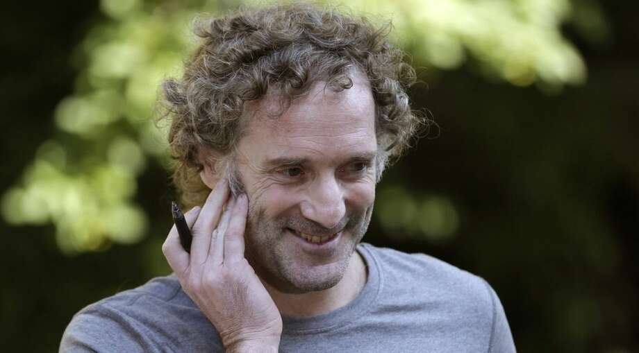 Peter Theo Curtis smiles as he talks with reporters outside his mother's home in Cambridge, Mass., Wednesday, Aug. 27, 2014. Curtis, a freelance reporter who wrote under the byline Theo Padno and who had been held hostage for about two years in Syria, returned to the U.S. Tuesday. (AP Photo/Charles Krupa)