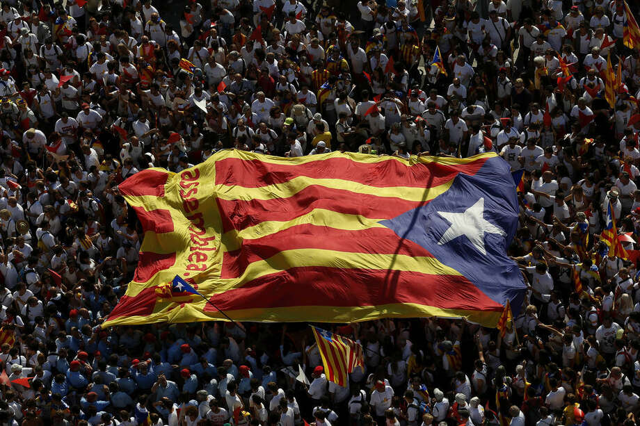 """FILE - In this Friday, Sept. 11, 2015 file photo, people carry a giant """"estelada"""" flag, a symbol of Catalonian pro-independence, during a demonstration calling for the independence of Catalonia in Barcelona. Spain's main banking associations warned Friday that a victory for Catalonia's secession drive would create severe banking problems for the new Mediterranean nation left outside the European Union. (AP Photo/Manu Fernandez, File)"""