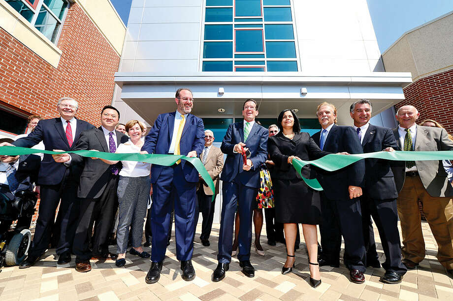 State and local officials join Gov. Dannel P. Malloy, center, to cut the ribbon during the J.M. Wright Technical School opening day ceremony Wednesday morning.