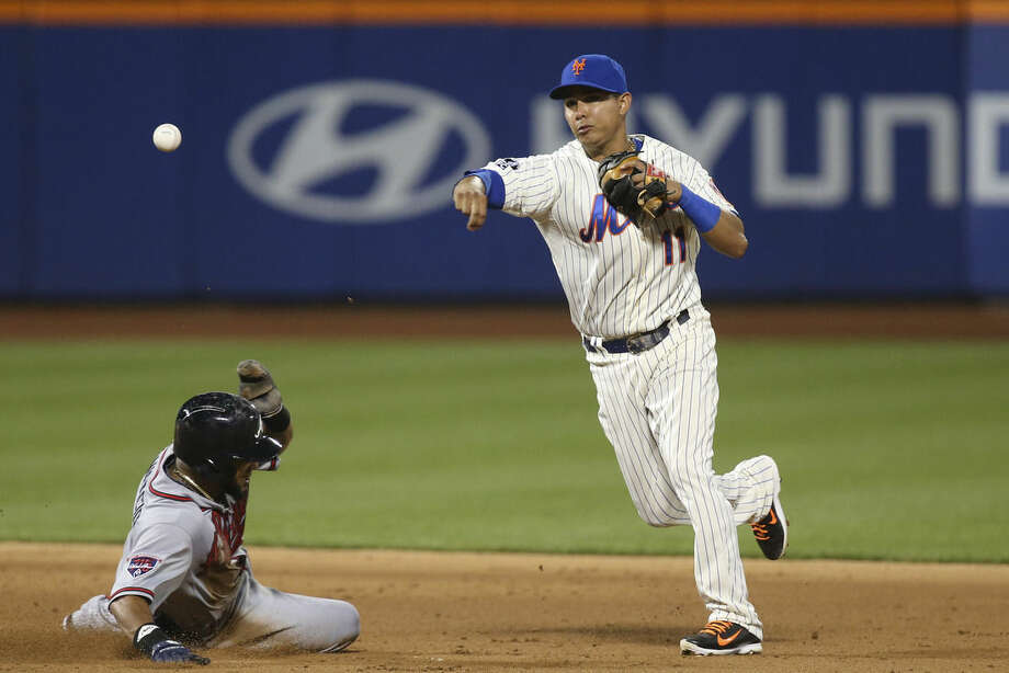 New York Mets shortstop Ruben Tejada (11) turns a double play as Atlanta Braves' Emilio Bonifacio, left, slides into second base in the ninth inning of a baseball game, Wednesday, Aug. 27, 2014, in New York. The Braves won 3-2. (AP Photo/John Minchillo)