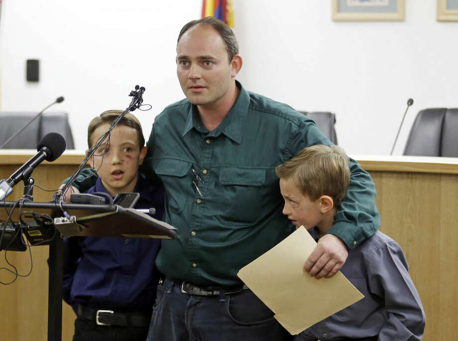"""FILE - In this Thursday, Sept. 17, 2015, file photo, Sheldon Black, Jr., and his two surviving sons speak to the media, in Colorado City, Ariz. Two grief-stricken fathers read statements that pivoted from the loss of their families to what one called """"religious genocide"""" against people who consider notorious, jailed leader Warren Jeffs a prophet of God. Black and Joseph N. Jessop said their families have been evicted from their homes, leaving them scrambling for a place to live """"because they will not forsake their religious beliefs."""" (AP Photo/Rick Bowmer, File)"""