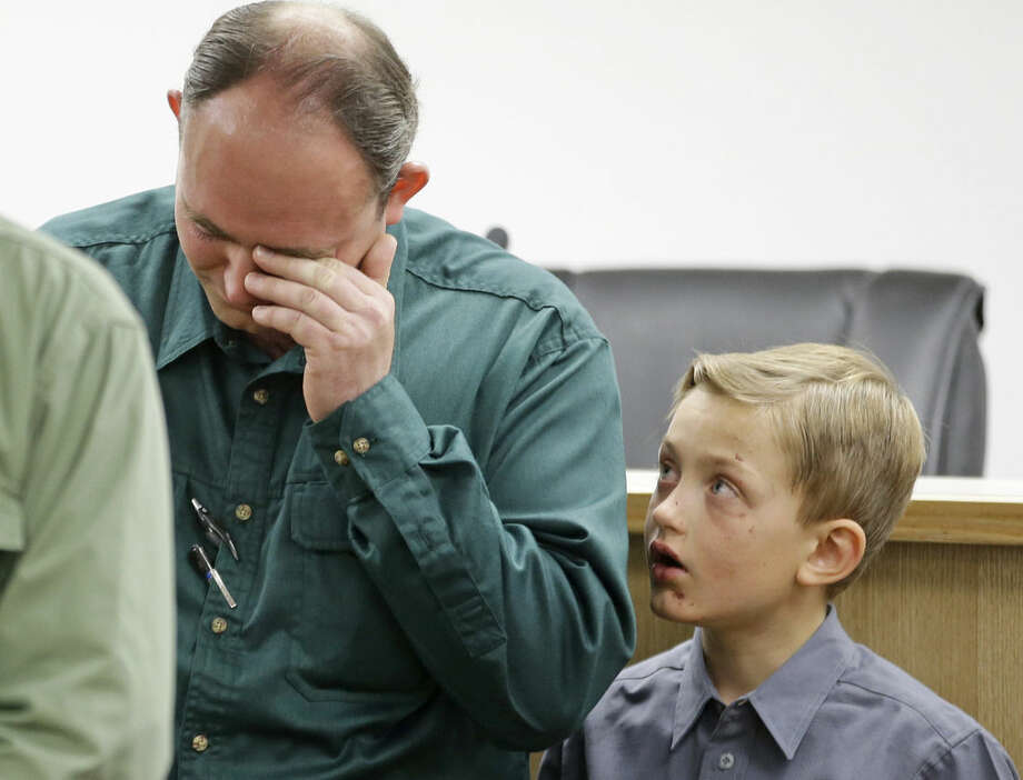 """FILE - In this Thursday, Sept. 17, 2015, file photo, Sheldon Black, Jr., lowers his head as one of his two surviving sons looks on during a news conference, in Colorado City, Ariz. Two grief-stricken fathers read statements that pivoted from the loss of their families to what one called """"religious genocide"""" against people who consider notorious, jailed leader Warren Jeffs a prophet of God. Black and Joseph N. Jessop said their families have been evicted from their homes, leaving them scrambling for a place to live """"because they will not forsake their religious beliefs."""" (AP Photo/Rick Bowmer, File)"""