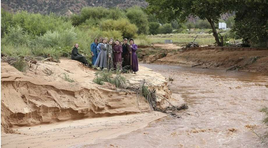 FILE - In this Tuesday, Sept. 15, 2015, file photo, community members look along a stream after a flash flood, in Colorado City, Ariz.After at least 12 women and children were killed by flash floods, two of the fathers of the victims made a rare public plea for Utah to leave them alone, laying bare authorities' delicate dance between investigating abuses and alienating the very people they're trying to help in the isolated communities of Hildale and Colorado City on the Utah-Arizona line. (AP Photo/Rick Bowmer, File)