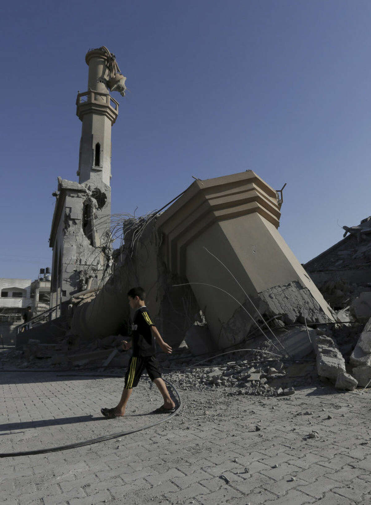 A Palestinian boy walks on the rubble of Omar Ibn Abed Al-Aziz mosque, which was hit by an Israeli strikes in Beit Hanoun, in the northern Gaza Strip, Wednesday, Aug. 27, 2014. The third Gaza War in six years appears to have ended in another sort of tie, with both Israel and Hamas claiming the upper hand. Their questionable achievements have come at a big price, especially to long-suffering Palestinians in Gaza. (AP Photo/Adel Hana)