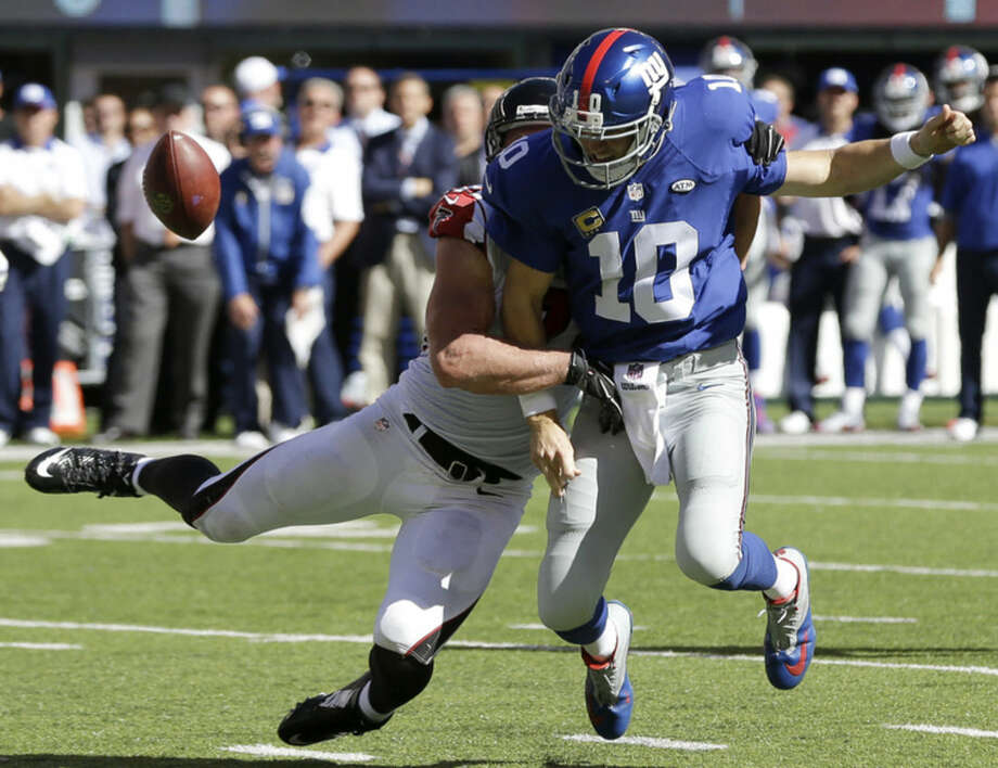 New York Giants quarterback Eli Manning, front, fumbles the ball as Atlanta Falcons outside linebacker Kroy Biermann makes the hit during the second half of an NFL football game, Sunday, Sept. 20, 2015, in East Rutherford, N.J. (AP Photo/Seth Wenig)