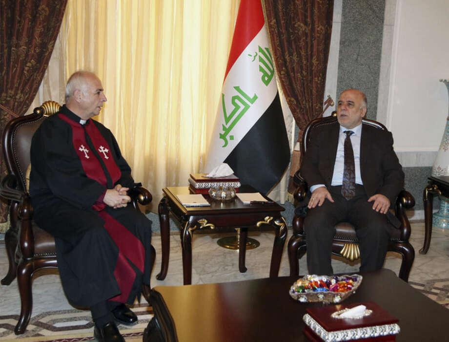 AP pool photo/Karim KadimIraqi premier-designate Haider al-Abadi, right, meets with Pastor Farouk Youssuf in Baghdad, Iraq, Thursday, Aug. 21.