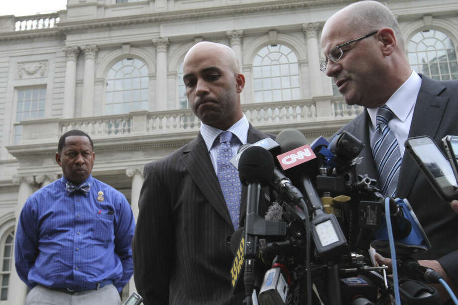 James Blake, center, listens as his attorney Kevin H. Marino, right, speaks to members of the media outside City Hall in New York after leaving the building Monday Sept. 21, 2015. Blake, a former tennis star, was tackled during a mistaken arrest by a New York City police officer on Sept. 9. (AP Photo/Tina Fineberg)