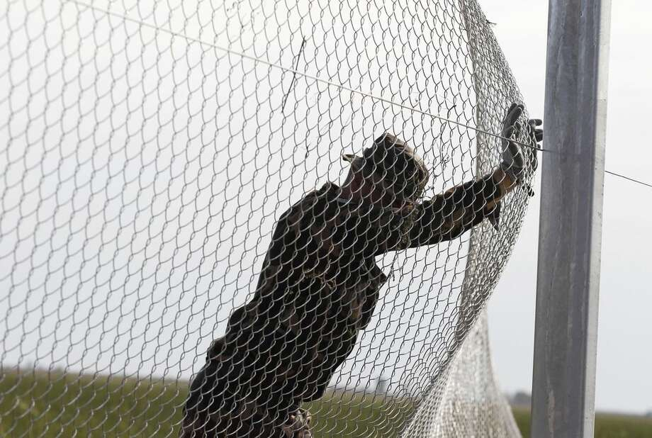 """A Hungarian soldier works on a fence that is being built at the border with Croatia, near the village of Beremend, Hungary, Tuesday, Sept. 22, 2015. Hungary's prime minister Viktor Orban said that millions of migrants are """"laying siege"""" to the borders of his country and of Europe, putting the continent in danger. (AP Photo/Petr David Josek)"""